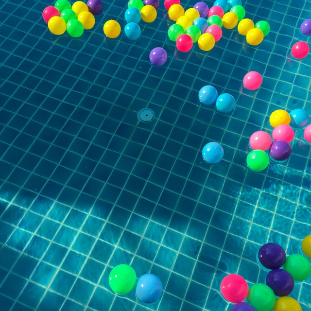 assorted-color-balls-floating-on-water-887821