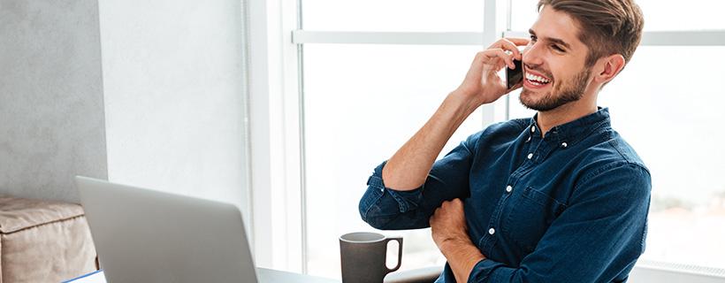 אדם יושב מול מחשב ומדבר בטלפון, מחייך