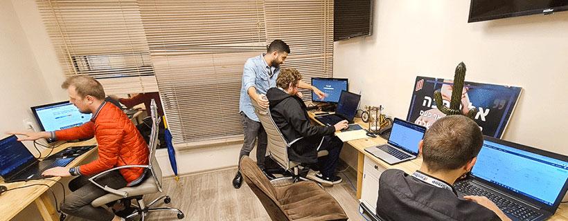 משרד עם מספר מקומות ישיבה, מנהל מראה לעובד משהו במחשב