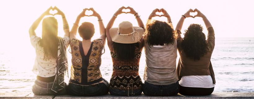 חמש נשים יושבות אחת ליד השניה ועושות צורת לב באצמעות הידיים