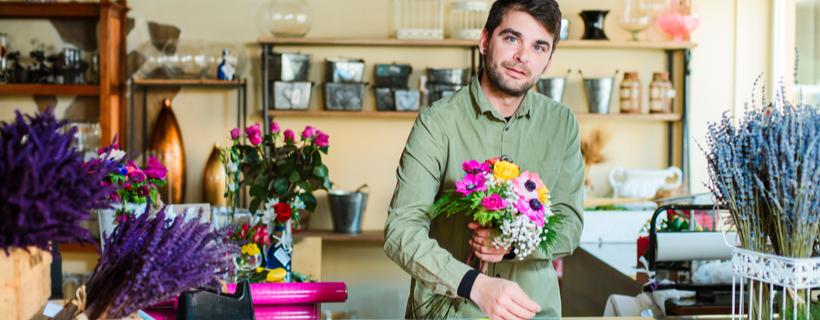 אדם בחנות מחזיק זר פרחים